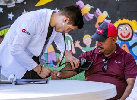 lab coat man checking patient's blood pressure