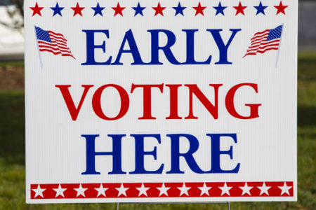 Early Voting Here sign. Take advantage of early voting, absentee voting and mail voting opportunities to make your voice heard. COVID-19