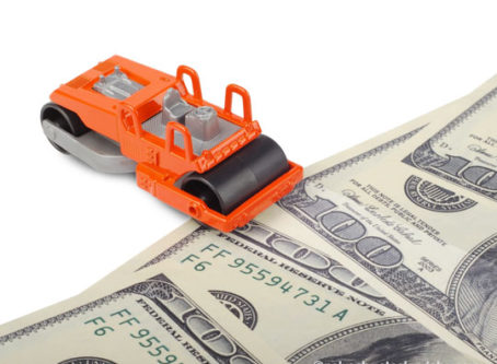 Toy paver machine, U.S. money. VMT tax on trucks is being considered by a federal agency.