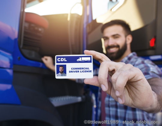Driver getting into cab, showing his CDL