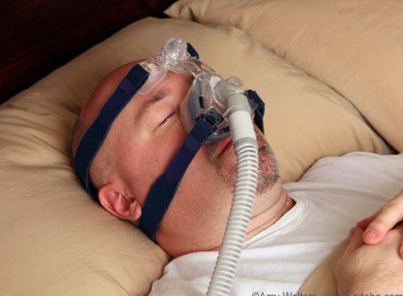 Man with sleep apnea wearing a CPAP breathing machine.