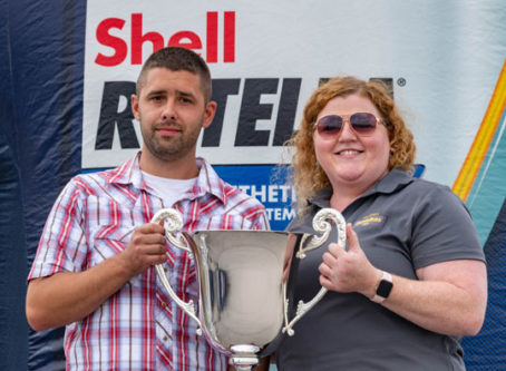 Keigan Nelson accepts the 2021 SuperRigs trophy from Heather Wales, Shell Rotella.